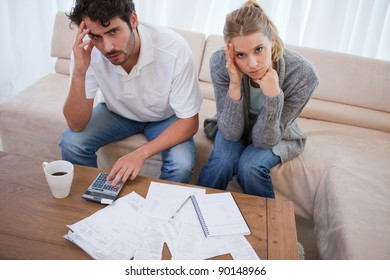Worried couple doing their accounting in their living room