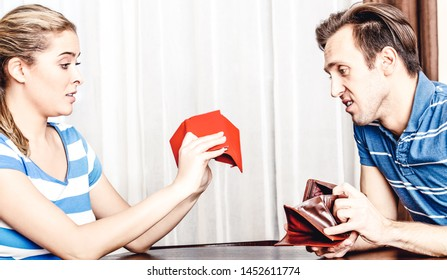 Worried couple looking at their empty wallets in home. Saving money concept.