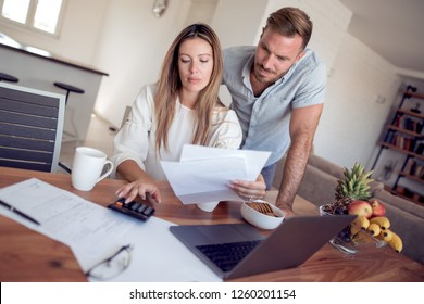 Worried couple reading together a letter sitting in a desk at home