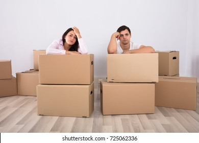 Worried Couple Sitting Near The Cardboard Boxes In Their New Home