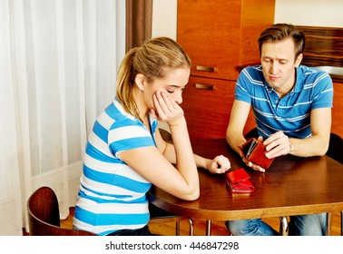 Worried couple sitting at the table with empty wallets