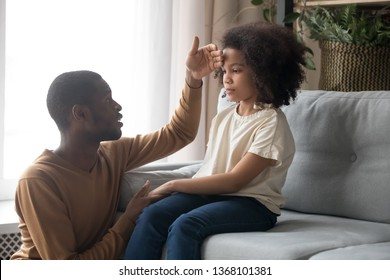 Worried dad father check temperature touch forehead of biracial unhealthy schoolgirl daughter sitting on sofa at home. Ill sick kid girl, parenting support, care love, treatment and healthcare concept