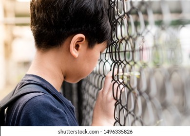 Worried depressed sad Asian tween boy (12 -15 years old) standing alone lean his head on iron wire fence in the school feeling lost. Bullying, Teen problem, Physical or emotional harm, Loneliness.