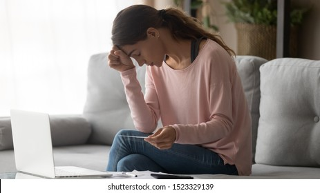 Worried depressed young woman upset by money bank debt financial problems holding calculating bills feeling stressed about high taxes expenses frustrated by bankruptcy sitting on sofa at home