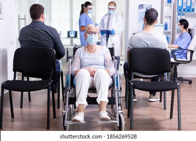 Worried disabled senior woman sitting in wheelchair in hospital waiting area for doctor examination. Old woman wearing face mask against coronavirus infection.