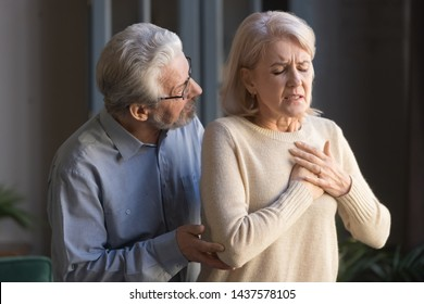 Worried elder senior husband helping supporting mature middle aged wife touching chest having heart attack feeling sudden pain heartburn heartache hurt at home, old couple health problems concept