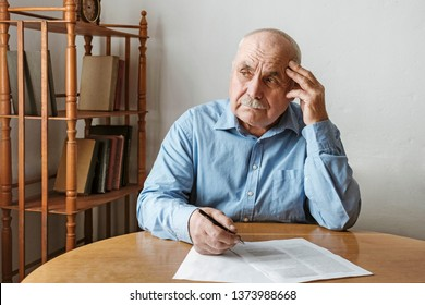 Worried elderly man completing a form seated at the table with his hand to his head looking aside with a thoughtful expression and frown