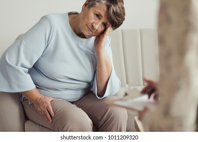 Worried elderly woman with a headache during a meeting with counselor