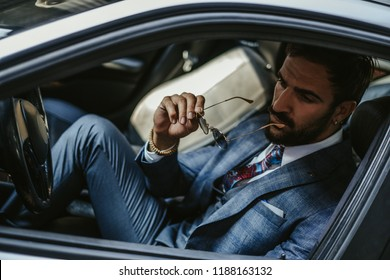Worried entrepreneur sitting in the car and holding his sunglasses