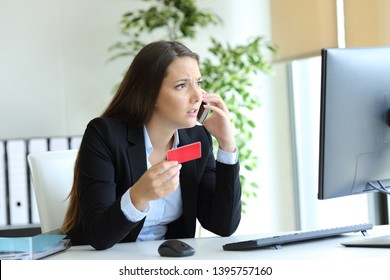 Worried executive holding credit card claiming on phone at office