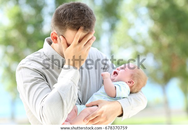 Worried father and baby crying outdoors