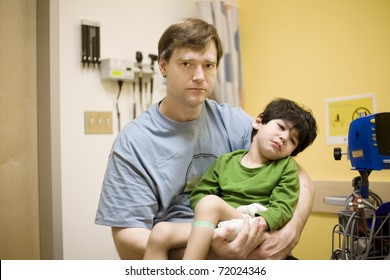 Worried father holding his sick disabled son in doctor's office