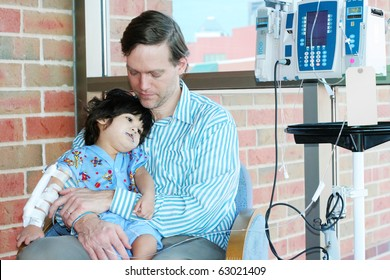 Worried father holding sick child in Hospital