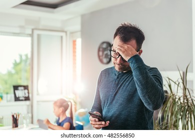 Worried father looking at smart phone and holding hand on forehead, in background his daughter doing homework