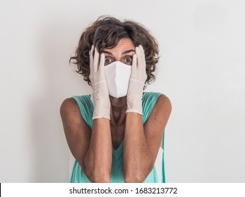 worried and fearful woman protecting from corona virus covid-19 wearing a white face mask and medical gloves having hands in her face on neutral background