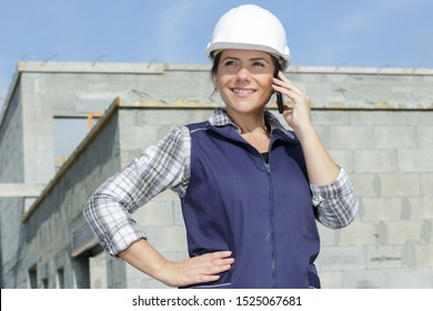 worried female contractor wearing hard hat on site using phone