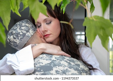 Worried female partner or wife holding her soldier husband dressed in uniform before he leaves home