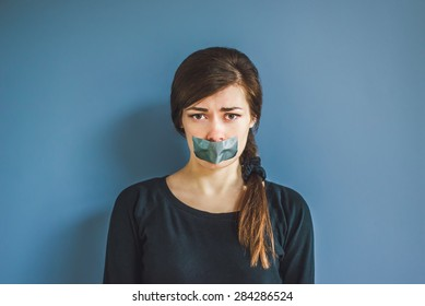 Worried girl with duct tape over her mouth
