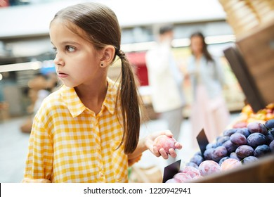 Worried girl with pony tails wearing checkered shirt standing at food shelves and holding plum while stealing it in food store