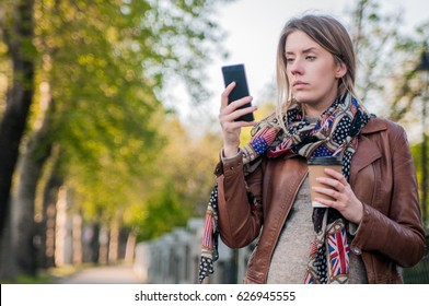 Worried Hipster teenager girl looking at her smart phone in a park with an unfocused background. Closeup portrait upset sad skeptical woman talking texting on phone displeased with conversation