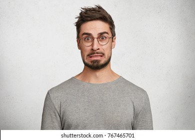 Worried indignant bearded male can`t understand something, has puzzled expression, wears casual clothes and spectacles, isolated over white background. Human facial expressions and feelings.