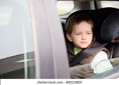 Worried little boy in car safety seat. Looking through the window. Children car safety concept.