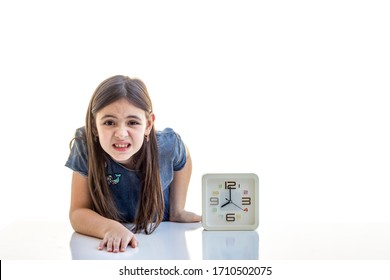 Worried little girl with clock at white studio background, copy space. Being late, time is the most precious resource concept.