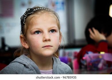 Worried little girl in school with her friends arround