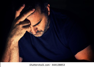 Worried lonely man with one hand on his forehead