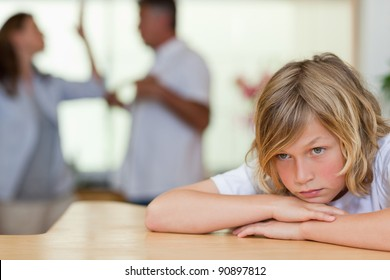 Worried looking boy with his fighting parents behind him