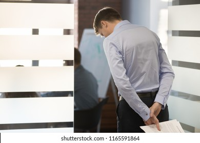 Worried male employee waiting his turn to enter conference room, man nervous before making presentation for colleagues, frustrated worker afraid join company meeting to present business report