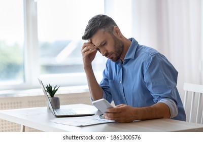 Worried male freelancer looking at smartphone screen while working at home office, received bad news, got scam message, thoughtful man touching forehead with concerned face expression, copy space