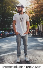 Worried man with hands in his pockets standing on the sidewalk and thinking