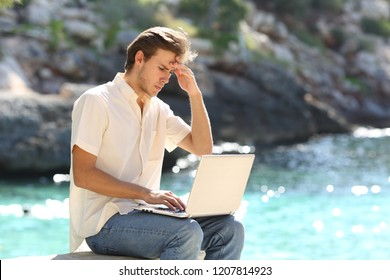 Worried man reading bad news online in a laptop on vacation on the beach