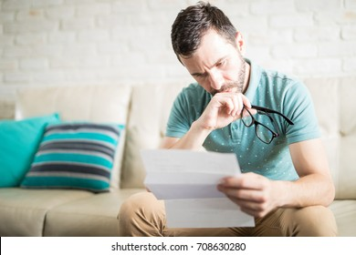 Worried man reading his mail and monthly bills and holding his glasses in his hands