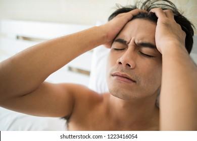 Worried man sitting on bed in the morning, serious thinking something
