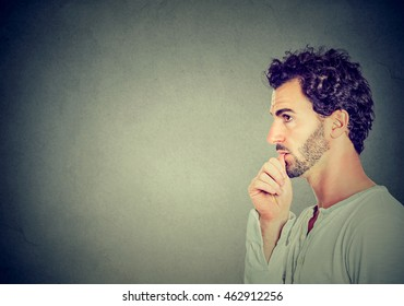 Worried man sucking his thumb isolated on gray wall background
