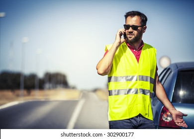 Worried man talking by cellphone with insurance company after car breakdown.