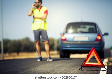 Worried man talking by mobile phone with insurance company after car breakdown.