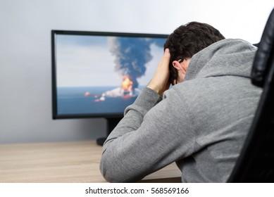 worried man watching (on TV) environmental disaster (oil platform explosion)