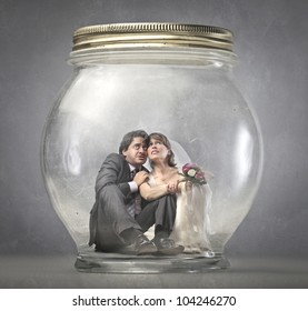 Worried married couple trapped in a glass jar