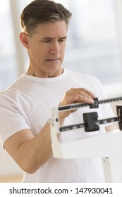 Worried mature man checking his weight on balance scale at health club