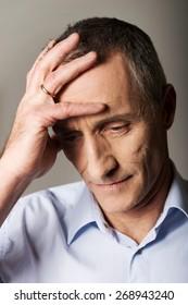 Worried mature man touching his head.