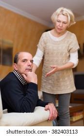 Worried mature woman assuaging man of anger indoors. Focus on man
