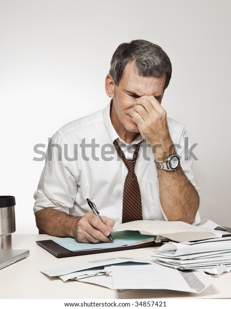 Worried, middle age man rubbing his forehead in pain, paying bills and writing checks