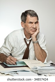 Worried middle age man sitting at desk paying bills, writing checks, and looking stressed out.