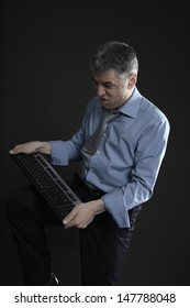 Worried middle aged businessman with computer keyboard against black background
