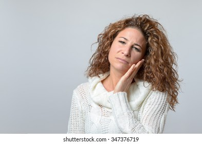 Worried middle aged woman looking at the camera with her hand raised to her cheek and a pained serious expression, over grey with copyspace