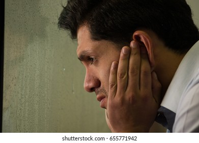 Worried mirrored young man is depresed, gray background