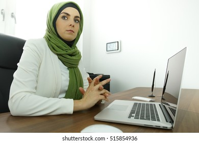 Worried muslim woman with hijab working in home office on laptop and typing